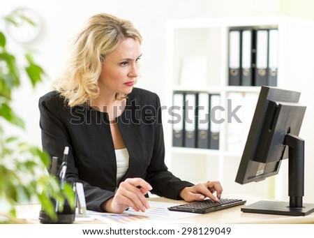 Businesswoman working with laptop at the office - stock photo