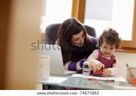 businesswoman working with laptop computer at home and playing with her baby girl. Horizontal shape, front view, waist up - stock photo