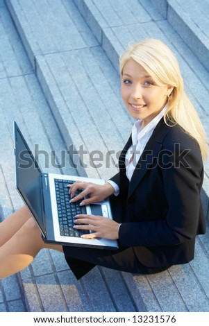 Businesswoman working with laptop computer, looking at camera - stock photo