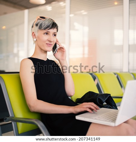 Businesswoman working with portable computer while talking at the phone at Charles de Gaulle airport, Paris.  - stock photo