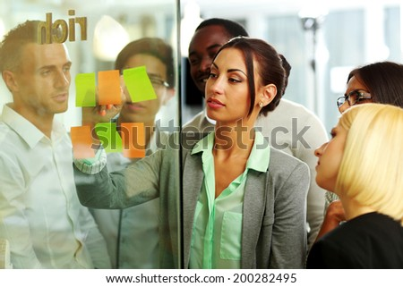 Businesswoman writes notes in the office - stock photo
