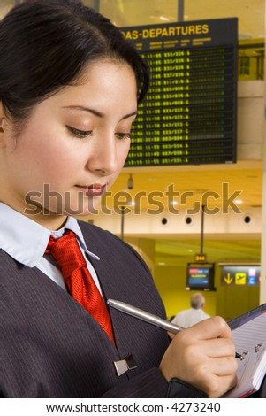businesswoman writing a report in an airport departure area.