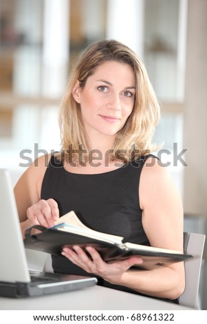 Businesswoman writing appointment on agenda - stock photo
