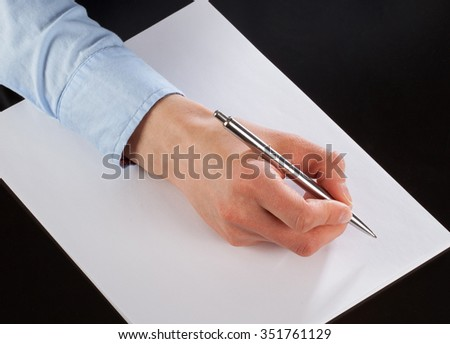 Businesswoman writing down notes on the paper (signing a document)