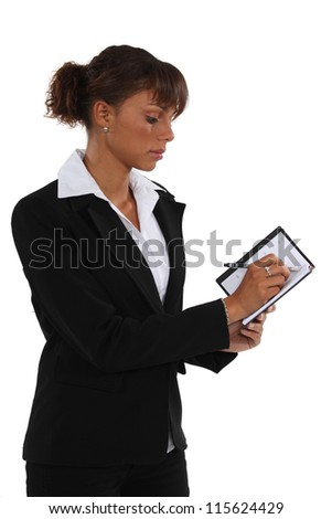Businesswoman writing in a diary
