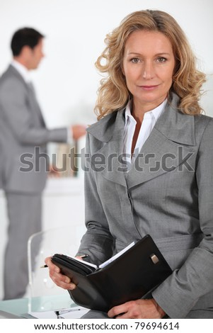 Businesswoman writing in a leather bound agenda - stock photo