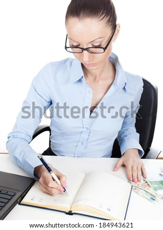 Businesswoman writing in daily planner book - stock photo