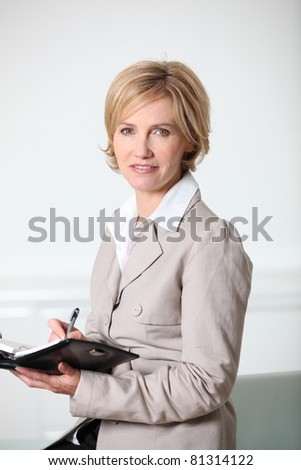 Businesswoman writing in diary - stock photo