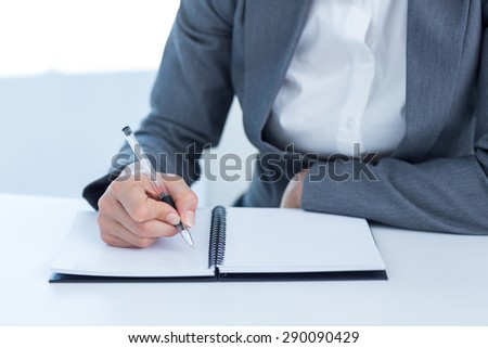 Businesswoman writing in her diary in the office