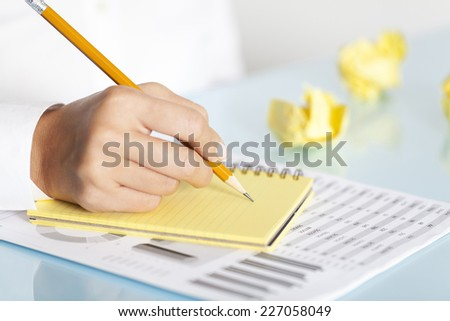 Businesswoman writing notes in a yellow notepad and crumpled papers around her