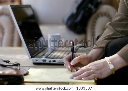 Businesswoman Writing Notes next to her Laptop Computer in a Hotel Atrium (shallow focus point on hand with pen). - stock photo