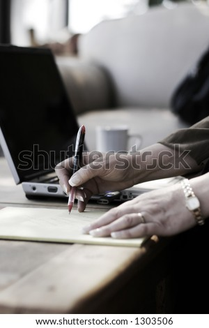 Businesswoman Writing Notes next to her Laptop Computer in a Hotel Atrium (slight color, shallow focus point on hand with pen). - stock photo
