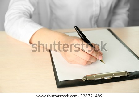 Businesswoman writing on document - stock photo