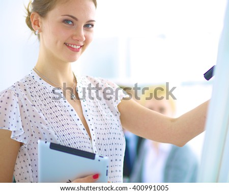 Businesswoman writing on flipchart while giving presentation to colleagues in office - stock photo