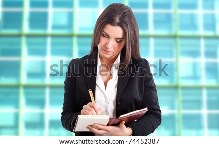 Businesswoman writing on her agenda, nice blurred background - stock photo
