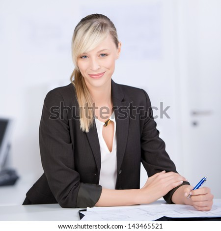 Businesswoman writing on her documents at the office