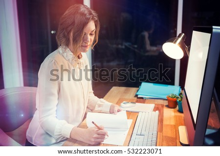 Businesswoman writing on paper at desk in office