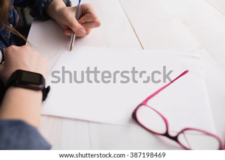 Businesswoman writing on sheet of paper at her desk - stock photo
