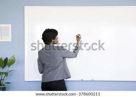 Businesswoman writing on whiteboard - stock photo