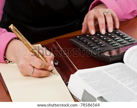 Businesswoman writing something on a notebook while using calculator