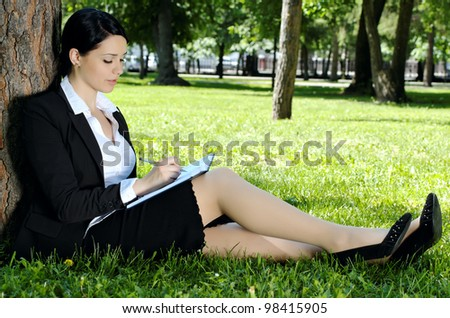 Businesswoman writing something to diary, sitting on green grass in park - stock photo