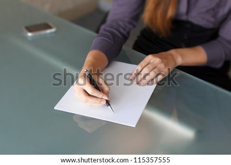Businesswoman writing with pen on paper - stock photo