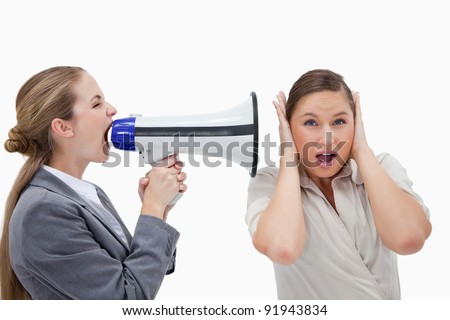 Businesswoman yelling at her coworker through a megaphone against a white background - stock photo