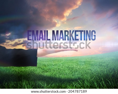 Businesswomans hand presenting the words email marketing against green field under orange sky - stock photo