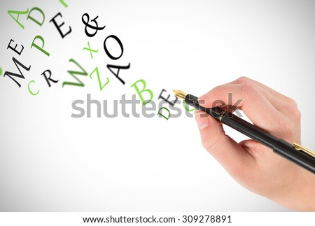 Businesswomans hand writing with fountain pen against letters