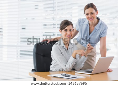 Businesswomen at desk smiling at camera with laptop in office - stock photo
