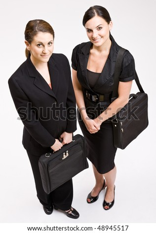 Businesswomen carrying briefcases - stock photo