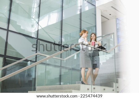 Businesswomen conversing while having coffee on steps in office - stock photo