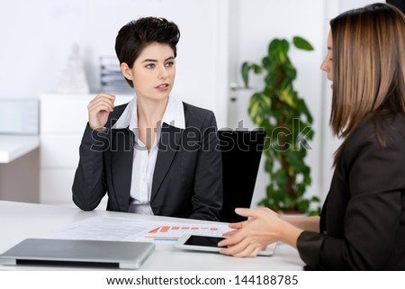 Businesswomen discussing in meeting at desk in office - stock photo