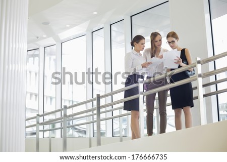 Businesswomen discussing over paperwork against railing - stock photo