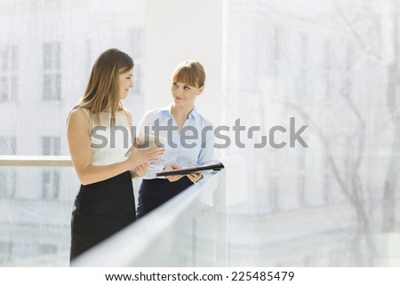 Businesswomen discussing over tablet PC while standing by railing in office - stock photo
