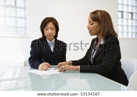 Businesswomen discussing paperwork at office desk. - stock photo