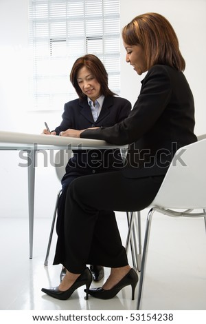 Businesswomen discussing paperwork at office desk smiling. - stock photo