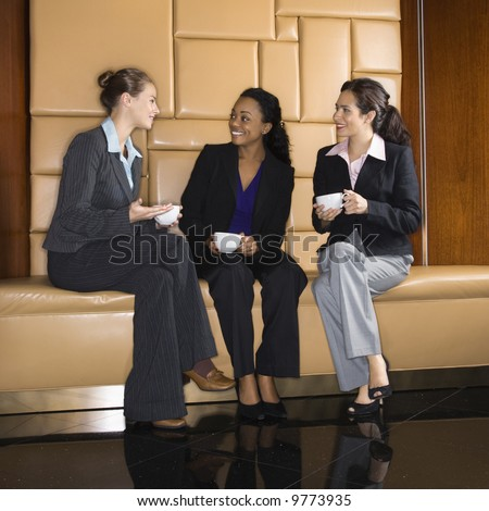 Businesswomen drinking coffee and conversing. - stock photo