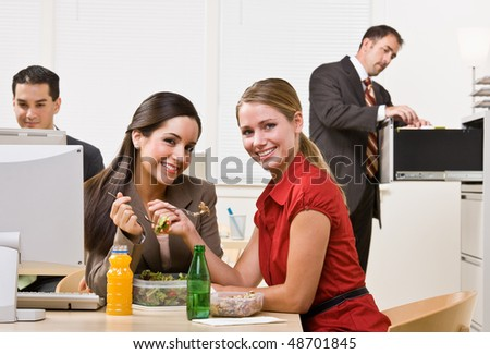 Businesswomen eating salad for lunch - stock photo