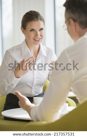 Businesswomen explaining to male colleague at office lobby - stock photo