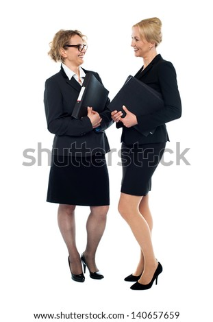 Businesswomen holding documents and interacting - stock photo