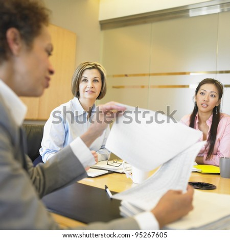 Businesswomen holding papers in meeting