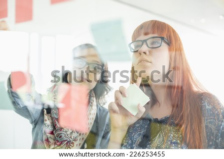 Businesswomen reading sticky notes on glass wall in creative office - stock photo