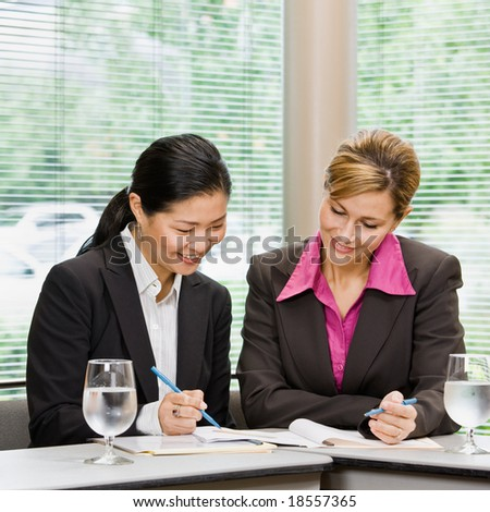 Businesswomen reviewing paperwork in conference room - stock photo