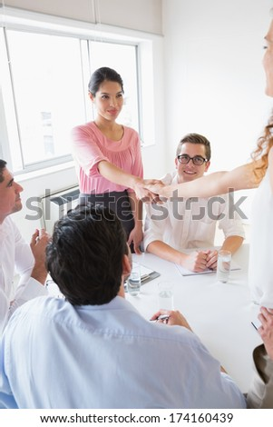 Businesswomen shaking hands at conference table during meeting in office - stock photo