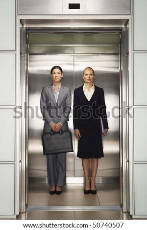 Businesswomen Side by Side in Elevator, portrait, front view - stock photo