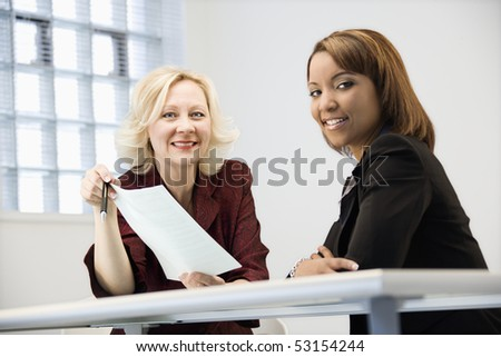Businesswomen sitting at office desk going over paperwork. - stock photo