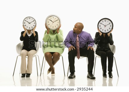 Businesswomen sitting holding clocks over faces while African-American businessman looks on. - stock photo