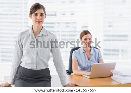 Businesswomen smiling at camera with one sitting and one standing at desk in office - stock photo