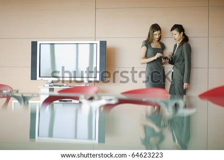 Businesswomen speaking, desk on foreground - stock photo